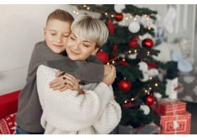 穿着白色毛衣的漂亮妈妈一家人在圣诞装饰_10704913