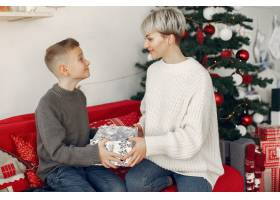 穿着白色毛衣的漂亮妈妈一家人在圣诞装饰_10704921