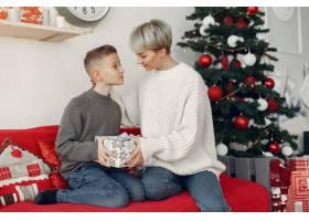 穿着白色毛衣的漂亮妈妈一家人在圣诞装饰_10704922