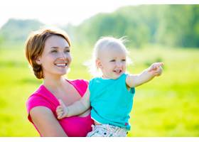 快乐的母亲和蹒跚学步的儿子在野外户外肖_11577579