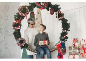 穿着白色毛衣的漂亮妈妈一家人在圣诞装饰_10704932