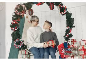 穿着白色毛衣的漂亮妈妈一家人在圣诞装饰_10704935