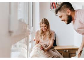 穿着粉色T恤的年轻女孩在玩狗而她的男朋_12432021