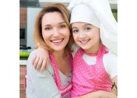 穿着粉色围裙的幸福微笑的母女在厨房里的肖_11599276