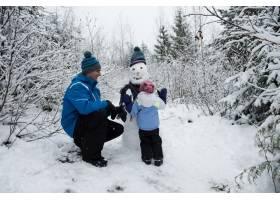 快乐的父亲看女儿堆雪人_11183527
