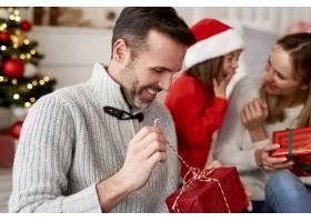 快乐的男人打开圣诞礼物_11725884
