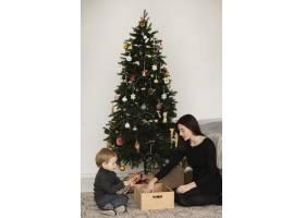 母子俩在圣诞树旁玩耍_10850886