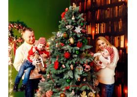 美丽的一家人穿着暖和的毛衣带着孩子在绿_1471477