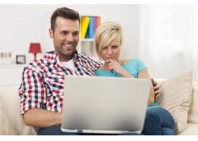 年轻夫妇坐在沙发上在家使用笔记本电脑_10675067