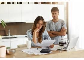 年轻夫妇检查他们的家庭预算_10113761