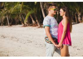 年轻漂亮的情侣走在泰国热带海滩拥抱欢_11083825