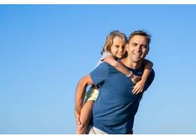 快乐的爸爸背着快乐的女孩父女俩在户外享_11298030