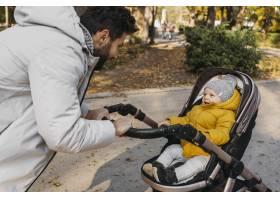 快乐的男人带着他的孩子坐在户外的婴儿车里_11904680