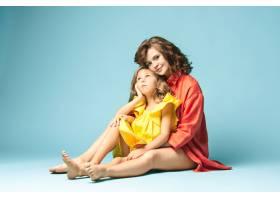 怀孕的母亲和十几岁的女儿蓝色背景上的家_9060052
