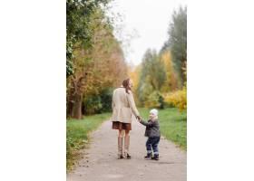 妈妈和儿子一起在秋天的公园散步和玩耍_11035197