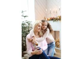 妈妈和女儿在圣诞装饰的客厅里_9389239