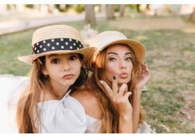 戴着帽子的黑眼睛女孩和妈妈在绿色公园享受_10485157