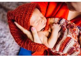 戴着红帽子的漂亮孩子睡在母亲温柔的怀里_1617094
