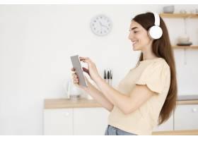 戴着耳机的侧视女子从她的笔记本电脑中选择_10700487