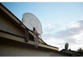 房顶上破碎的篮筐的低角投篮_10860880