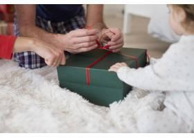 婴儿与父母一起打开圣诞礼物特写_11725329