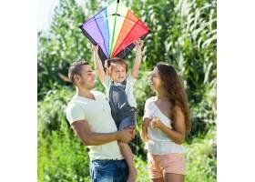 抱着风筝的小女孩坐在父亲的怀里_1632129