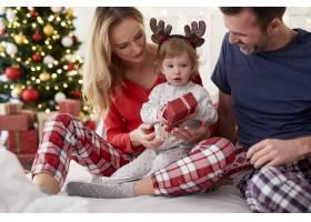 宝宝在床上和父母一起打开圣诞礼物_11725826