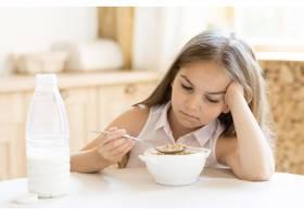 无聊的年轻女孩早餐吃麦片_10604635