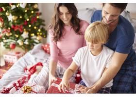 家人在床上打开圣诞礼物_11727653