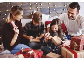 家人在床上打开圣诞礼物_11756984
