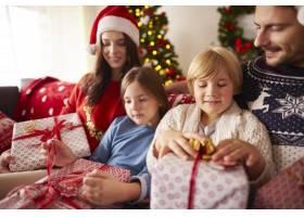家庭在家中打开圣诞礼物_11820635