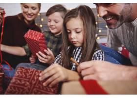 家庭在床上打开圣诞礼物的特写_11757097