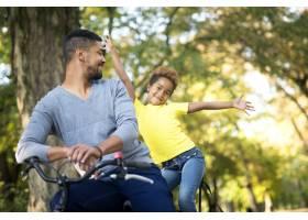 可爱的女孩举起双臂父亲骑着自行车在公园_11139202