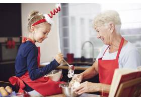 可爱的女孩在奶奶的帮助下做饭_11728066