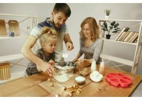 可爱的小女孩和她漂亮的父母在家里的厨房里_10521462