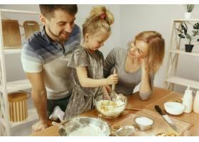 可爱的小女孩和她漂亮的父母在家里的厨房里_10521463