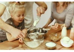 可爱的小女孩和她漂亮的父母在家里的厨房里_10521464