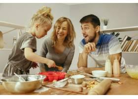 可爱的小女孩和她漂亮的父母在家里的厨房里_10521465