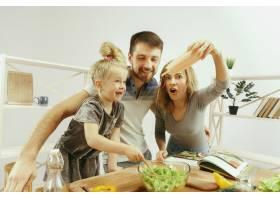可爱的小女孩和她漂亮的父母在家里的厨房里_10542911