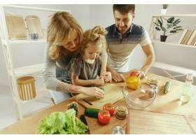 可爱的小女孩和她漂亮的父母在家里的厨房里_10542915