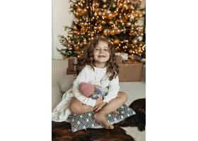 可爱的小女孩坐在圣诞树上带着玩具的枕头上_11146270