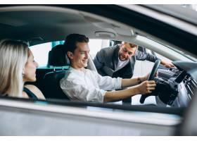 年轻家庭在汽车展厅买车_5508134