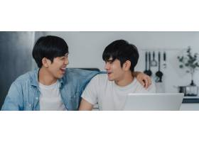 年轻的同性恋情侣在现代家庭中一边使用笔记_6139038
