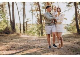 年轻的一家人带着可爱的小女儿在夕阳的森林_10298374