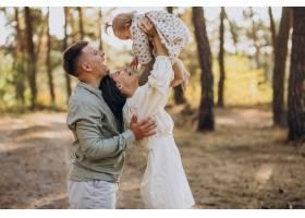 年轻的一家人带着可爱的小女儿在夕阳的森林_10298385