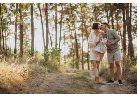 年轻的一家人带着可爱的小女儿在夕阳的森林_10298389