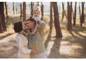 年轻的一家人带着可爱的小女儿在夕阳的森林_10298398