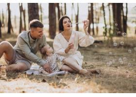 年轻的一家人带着可爱的小女儿在夕阳的森林_10298402