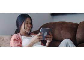 年轻的亚洲孕妇使用平板电脑搜索怀孕信息_6139075