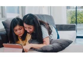 年轻的亚洲家庭和女儿在家中快乐地使用平板_6142518